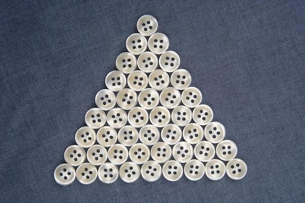 Plastic glanzende knopen voor kleding op een stoffenachtergrond.