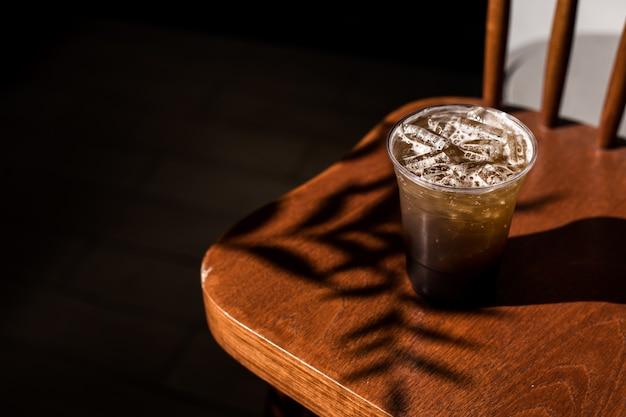 Plastic glas ijskoffie met sprankelende frisdrank op tafel