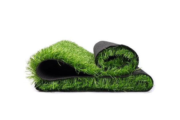 Plastic groen gras dat op witte muur wordt geïsoleerd.