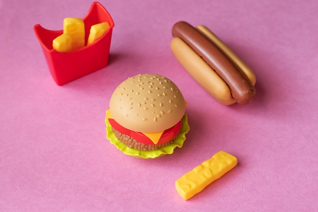 Plastic hamburger, salade, tomaat, frituren aardappelen met een hotdog op een roze achtergrond