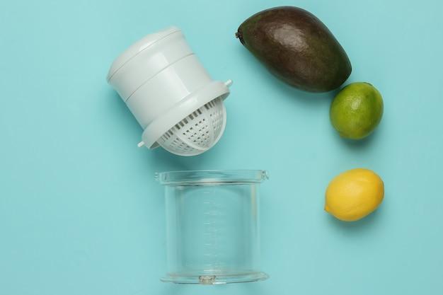 Plastic handmatige juicer en tropisch fruit op blauwe achtergrond. gezond voedselconcept. versgeperste sappen. bovenaanzicht