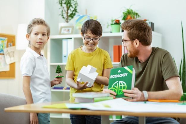 Plastic huis inspecteren. stralende donkerharige student in geel t-shirt die een klein huis laat zien aan zijn leraar tijdens ecologielessen