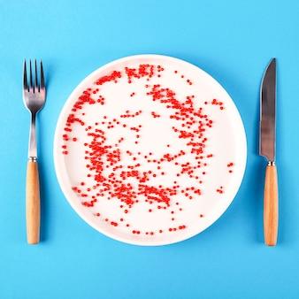 Plastic in een bord naast een mes en vork