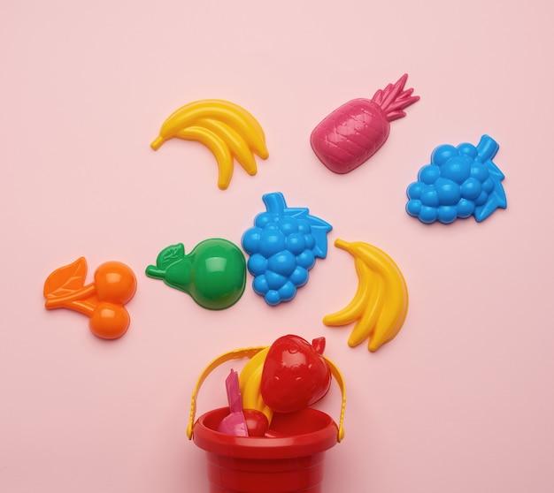 Plastic kinderspeelgoed in de vorm van fruit en een emmer op een roze achtergrond