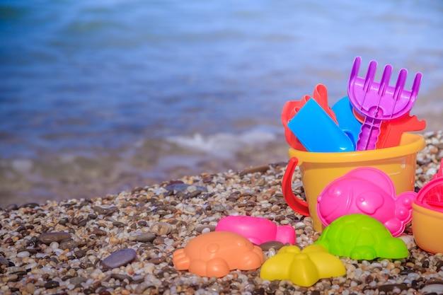 Plastic kinderspeelgoed voor zand op de zee. speelgoed voor kinderen. plastic zandspeelgoed. helder speelgoed.