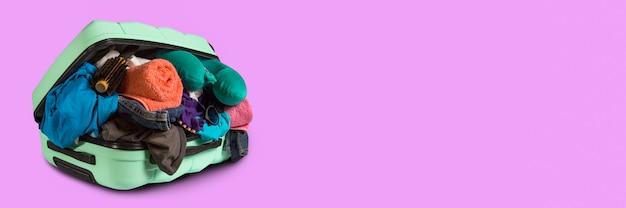 Plastic koffer met wielen, overvolle dingen op een roze achtergrond. reisconcept, vakantiereis, bezoek aan familieleden. banner