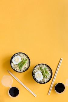 Plastic kommen instant noedels met eieren eetstokjes en sojasaus op papier achtergrond kopie ruimte.
