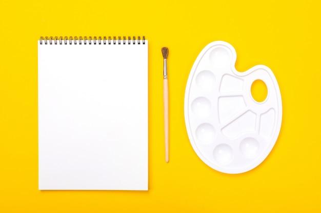 Plastic kunstpalet met album voor het schilderen en penseel op oranje achtergrond