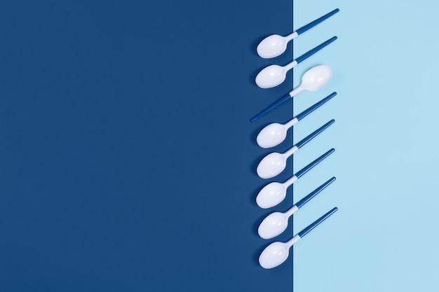 Plastic lepels op blauwe tafel.