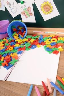 Plastic letters van het alfabet op school bureau