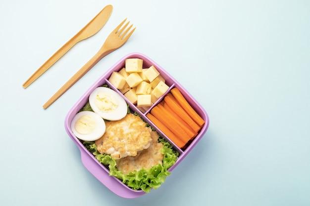 Plastic lunchbox met vork en mes op blauwe achtergrond. ruimte kopiëren