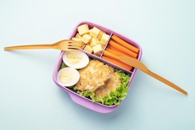 Plastic lunchbox met vork en mes op blauwe achtergrond