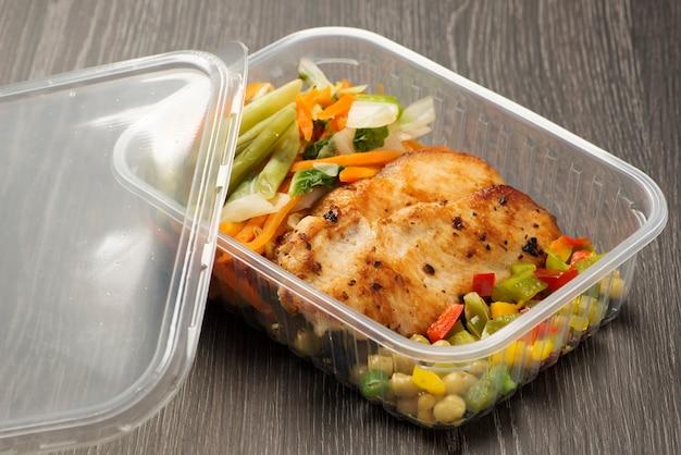 Plastic lunchdoos met gegrilde kipfilet en gekookte groenten.