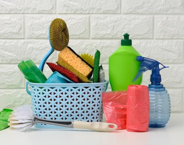 Plastic mand met borstels, ontsmettingsmiddel in een fles, rubberen handschoenen op de achtergrond van een witte bakstenen muur. huis schoonmaak artikelen set