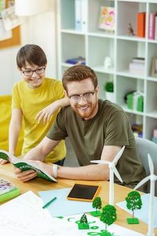 Plastic model ontdekken. glimlachende geïnteresseerde man in een heldere bril die een geopend boek draagt en aandacht schenkt aan zijn student om te modelleren
