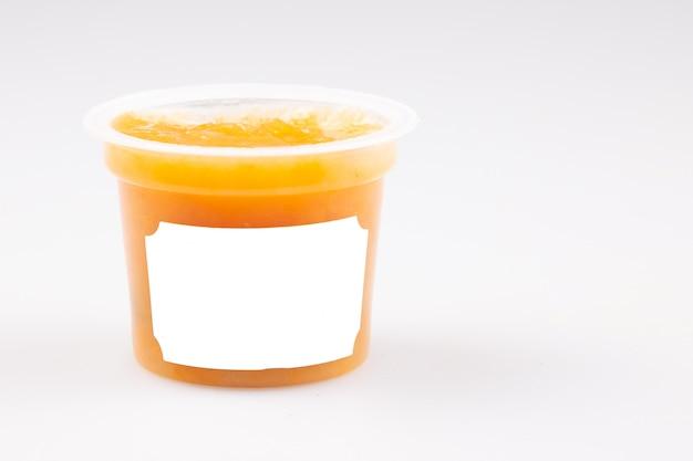 Plastic oranje pot met perzikcompote