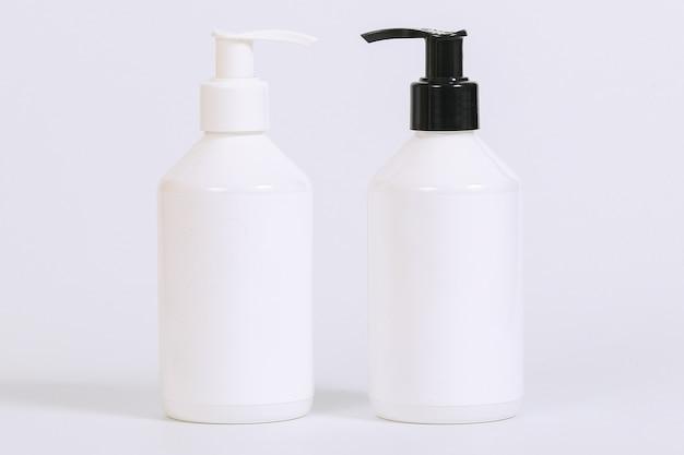 Plastic pompfles met wit etiket dat op witte achtergrond wordt geïsoleerd
