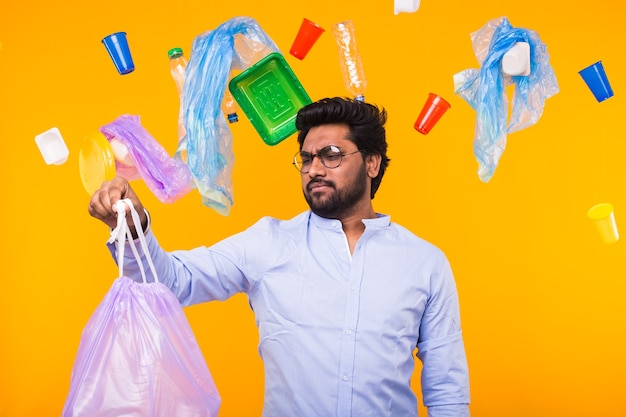 Plastic recyclingprobleem, ecologie en milieurampconcept - indische mens die vuilnis met walging op gele muur bekijkt.
