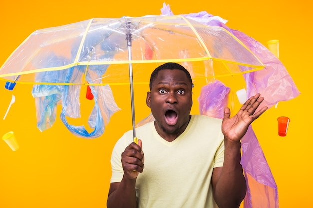 Plastic recyclingprobleem, ecologie en milieurampconcept - verrast afro-amerikaanse man op gele muur met afval. hij maakt zich zorgen over een ecologische ramp