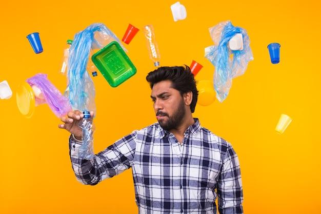 Plastic recyclingprobleem, ecologie en milieurampconcept - verraste indische mens die een plastic zak houdt