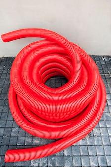 Plastic rode gegolfde buis voor afwatering op de tegel
