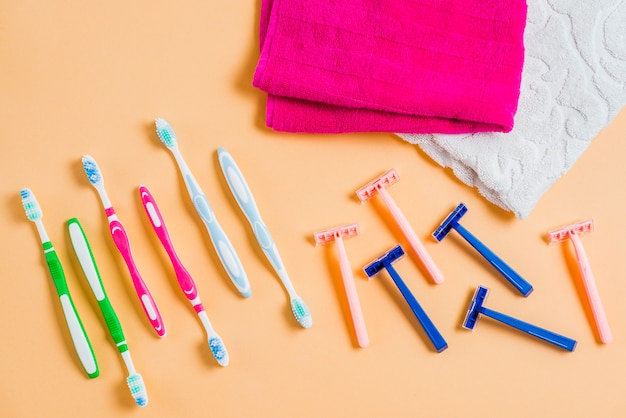 Plastic scheermes met tandenborstels en handdoek op gekleurde achtergrond