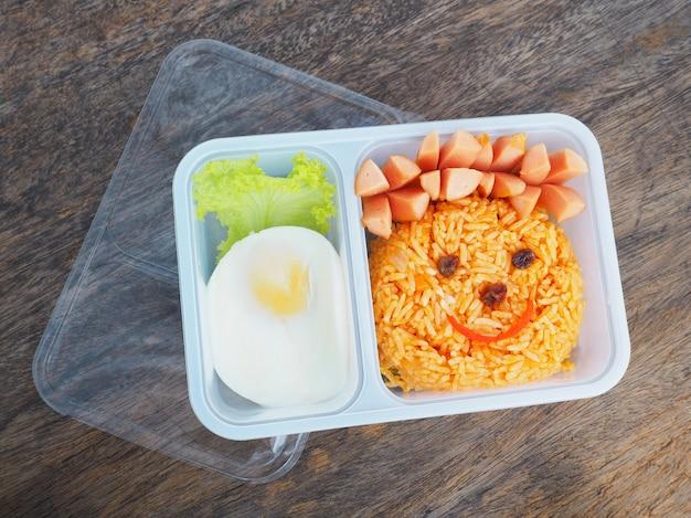 Plastic schoollunchdoos voor kinderen met grappig gezicht van gebraden rijst en ei