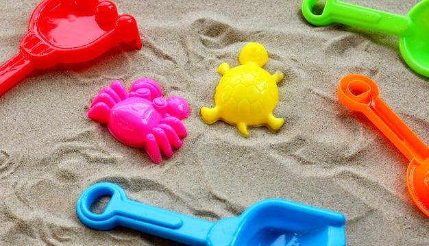 Plastic speelgoed, kleurrijke schoppen op zand.