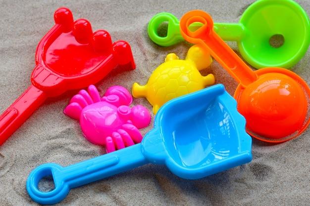 Plastic speelgoed, kleurrijke schoppen zand op zand