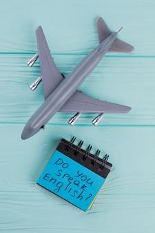 Plastic speelgoed passagiersvliegtuig en kleverig papier op blauwe houten ondergrond. boven weergave plat lag. spreek je engels op sticker.