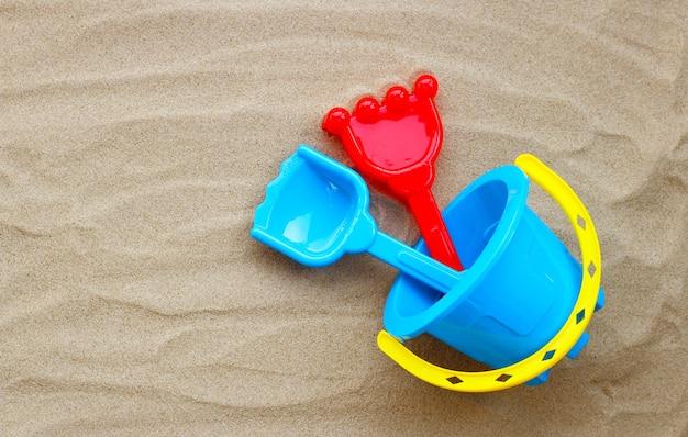Plastic speelgoed, schop en emmer op zand op witte achtergrond. zomer achtergrond concept