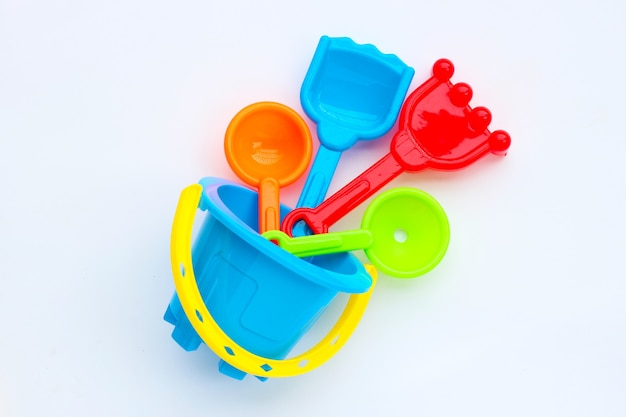 Plastic speelgoed, schop en emmer voor zand op wit oppervlak