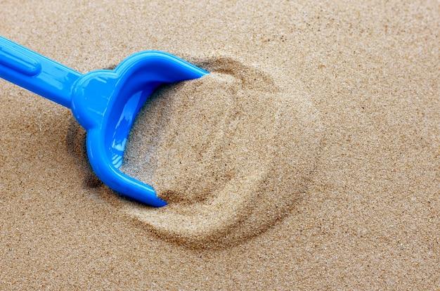 Plastic speelgoed, schop in zand. achtergrond concept