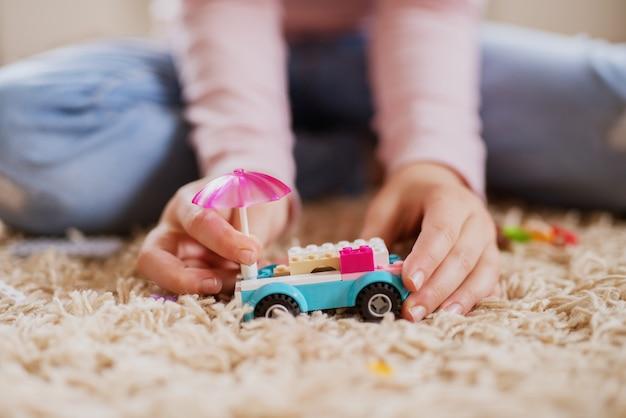 Plastic speelgoedauto van blokken en paraplu op het tapijt in focus voor kleine peuter meisje nemen met handen.