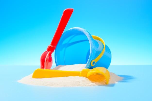 Plastic speelgoedemmer, hark en schep in het zand