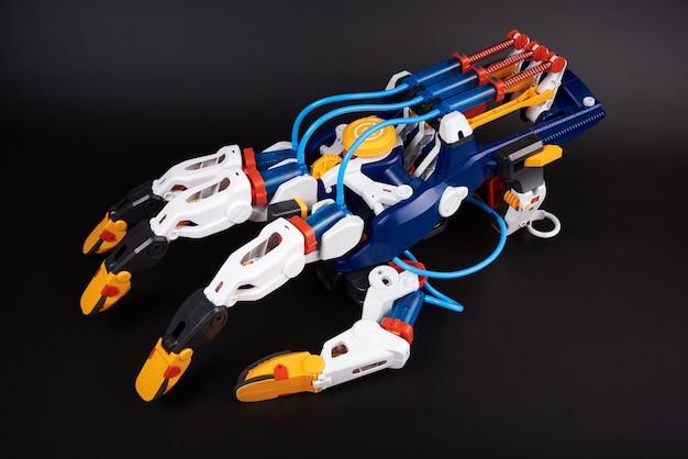 Plastic speelgoedrobotarm met hydraulisch vingerbewegingsmechanisme. geïsoleerd op zwart