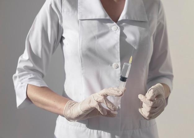 Plastic spuit met naald in handen van artsen of verpleegsters in handschoen