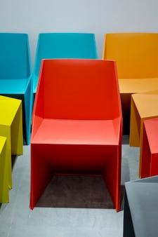 Plastic stoelen door rode, blauwe, oranje kleuren