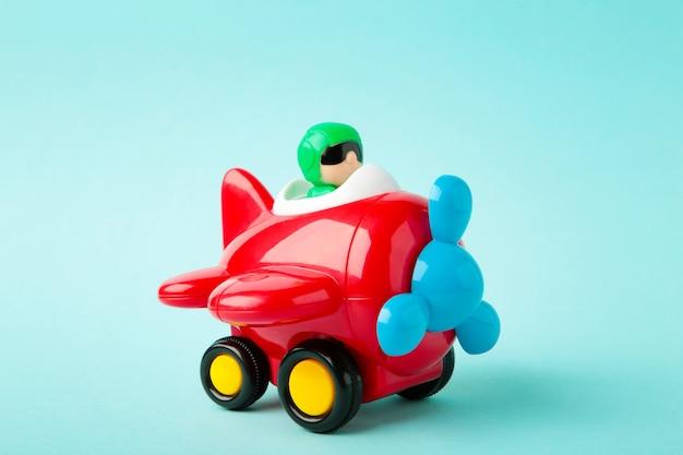 Plastic stuk speelgoed vliegtuig op blauwe achtergrond. vliegtuig
