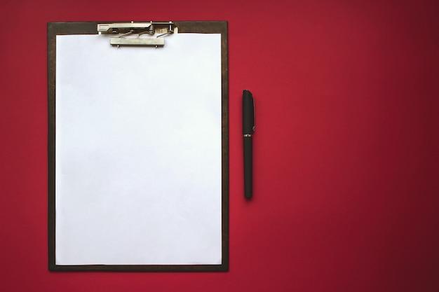 Plastic tablet met wit vel papier op de rode achtergrond. bovenaanzicht. concept van nieuwe kansen, ideeën, ondernemingen, innovaties.