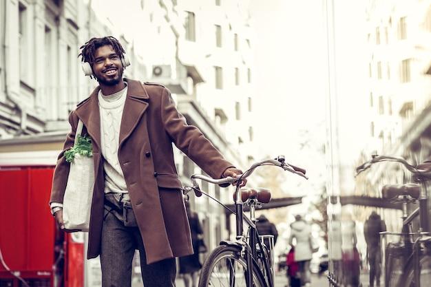 Plastic tas. tevreden bebaarde man die een glimlach op zijn gezicht houdt terwijl hij naar muziek luistert