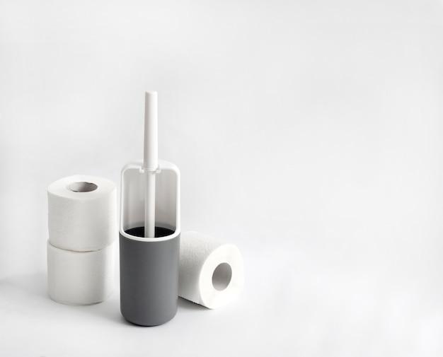 Plastic toiletborstel en toiletpapier op wit oppervlak