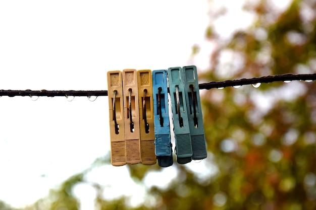 Plastic veelkleurige oude wasknijpers hangend aan een draad met regendruppels.