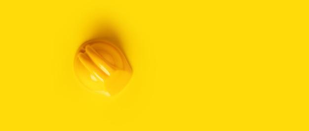 Plastic veiligheidshelm over gele achtergrond, panoramisch modelbeeld
