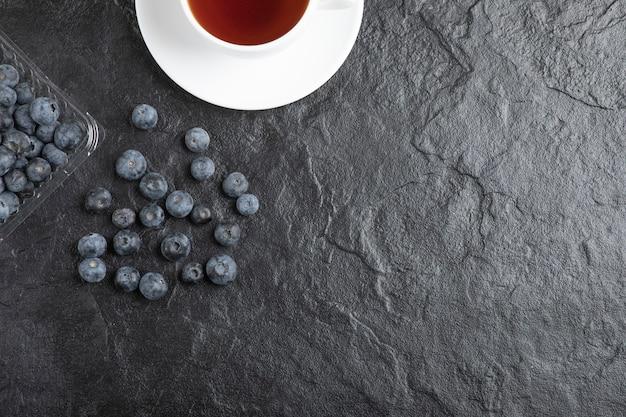 Plastic verpakking van heerlijke verse bosbessen met kop hete thee
