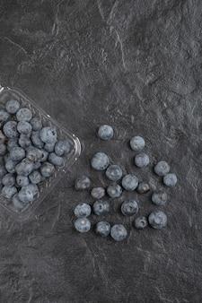 Plastic verpakking van heerlijke verse bosbessen op zwarte ondergrond