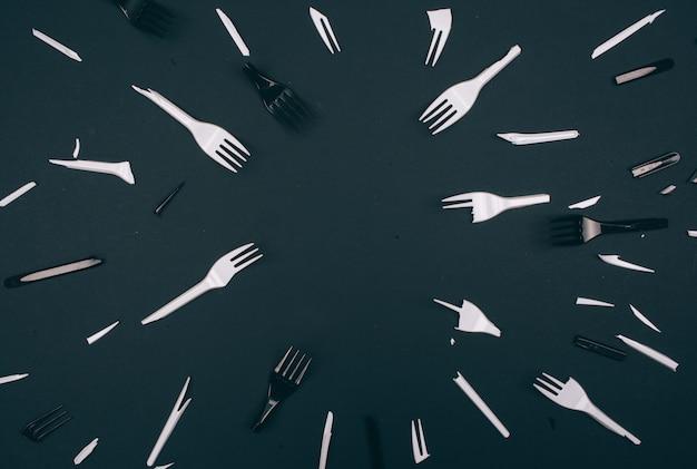 Plastic vervuiling concept. nee tegen plastic. gebroken witte en zwarte vorken voor eenmalig gebruik op donkere achtergrond. nieuwe regels om plastic afval te verminderen, eu-richtlijn. we kunnen onze planeet niet langer vervuilen.