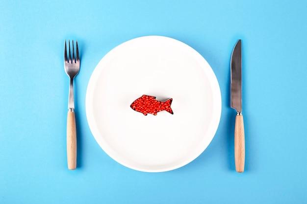 Plastic vis in een bord naast een mes en vork