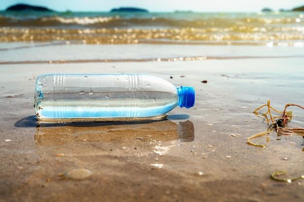 Plastic waterflessen op het strand, milieuconcept