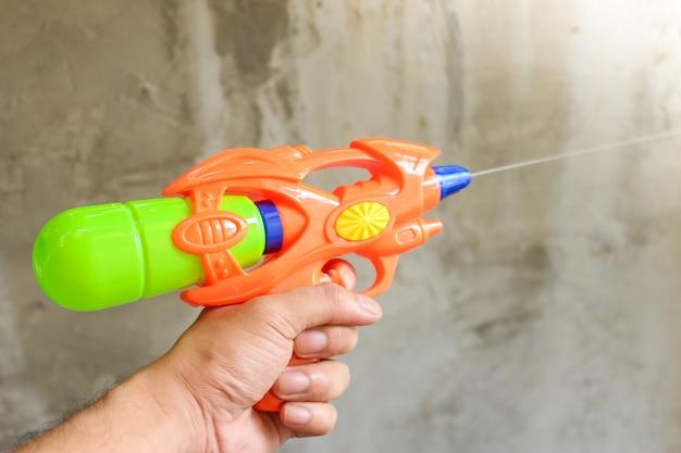 Plastic waterpistool dat op groene achtergrond wordt geïsoleerd